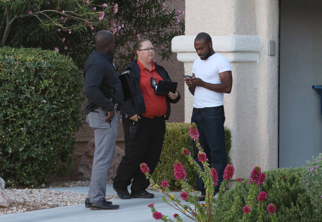 Investigators talk to a resident neat the scene where police investigate a shooting involving a ...