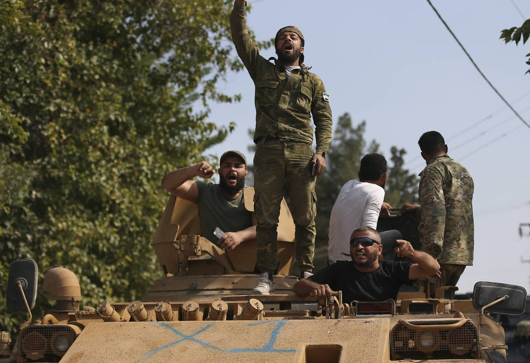 Turkish-backed Syrian opposition fighters on an armoured personnel carrier chant slogans as the ...