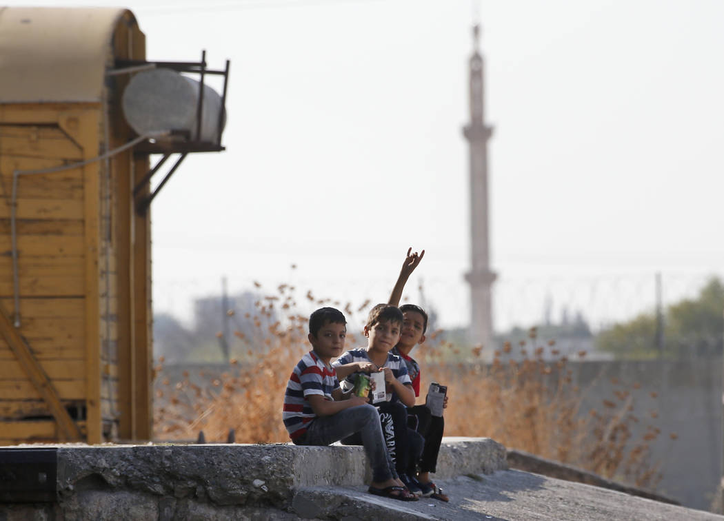 Children gesture to the camera in Akcakale Sanliurfa province, southeastern Turkey, at the bord ...