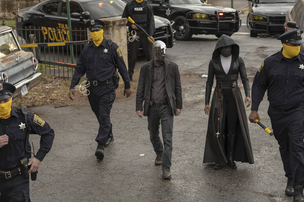 The mirror-masked Looking Glass (Tim Blake Nelson) and the hooded, black-robed Sister Night (Re ...
