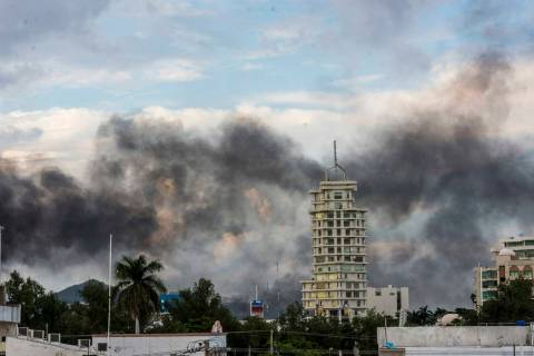 Smoke from burning cars rises due in Culiacan, Mexico, Thursday, Oct. 17, 2019. An intense gunf ...