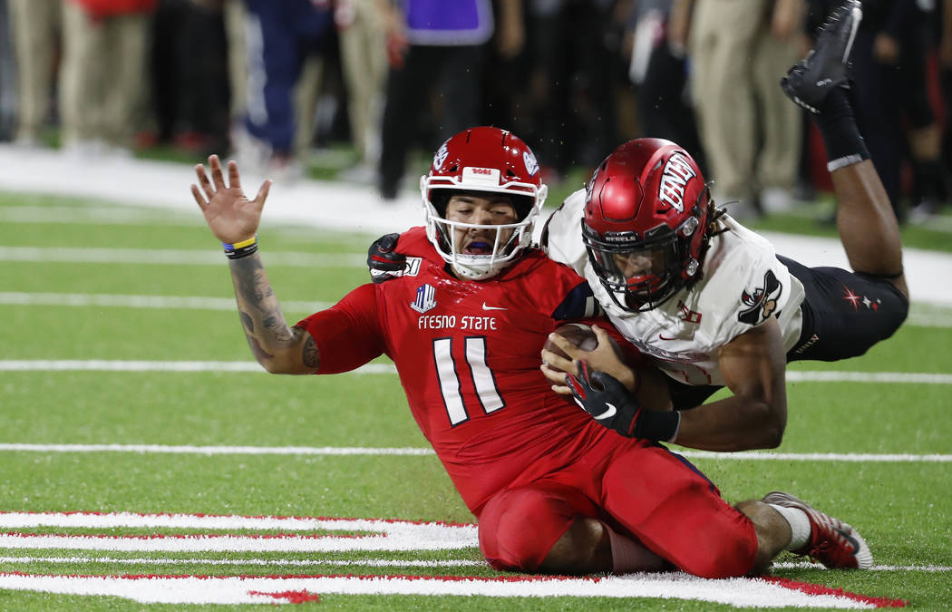 UNLV defensive back Evan Austrie tackles Fresno State quarterback Jorge Reyna during the first ...