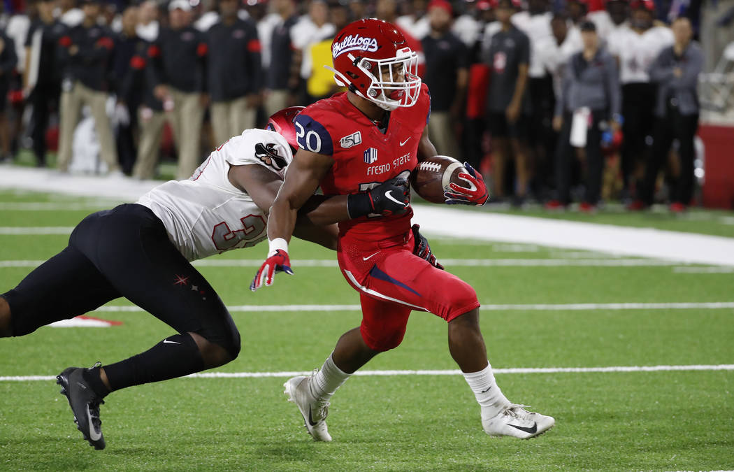UNLV linebacker Jacoby Windmon tries to tackle Fresno State running back Ronnie Rivers, who sco ...