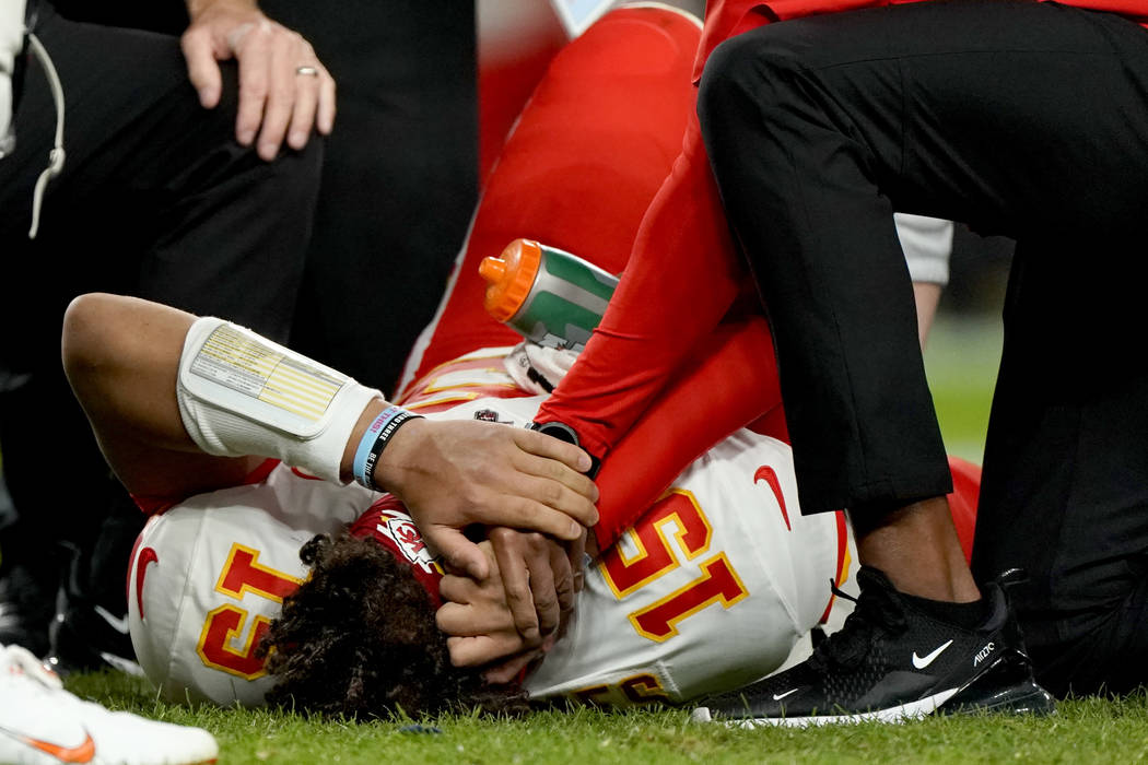Kansas City Chiefs quarterback Patrick Mahomes (15) is helped by trainers after getting injured ...