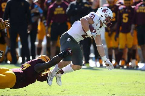 Washington State running back Max Borghi (21) is pulled down by Arizona State linebacker Darien ...