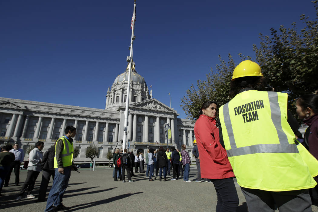 An evacuation team member stands with participants during an earthquake preparedness drill acro ...