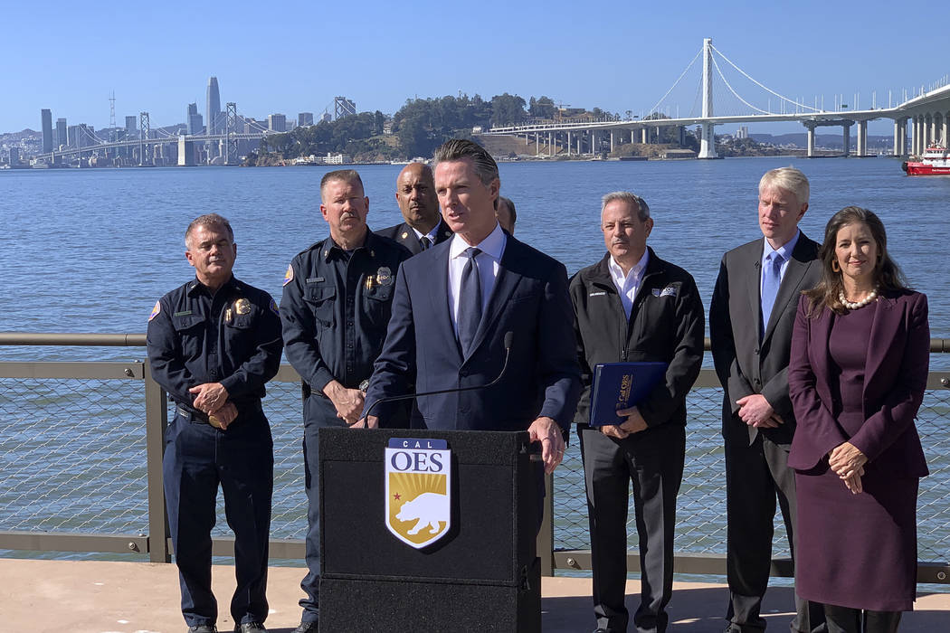 Gov. Gavin Newsom, center, speaks at a news conference with other officials to announce the sta ...