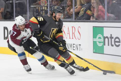 Golden Knights defenseman Jake Bischoff (45) fights for possession with Colorado Avalanche left ...