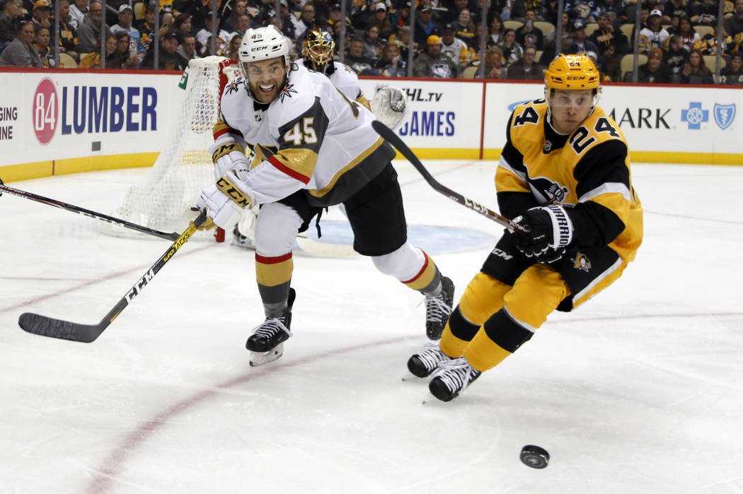 Vegas Golden Knights' Jake Bischoff (45) and and Pittsburgh Penguins' Dominik Kahun (24) chase ...