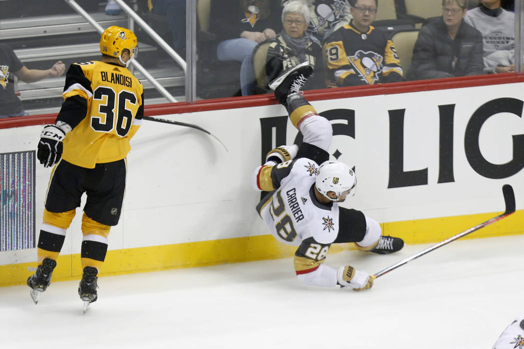 Vegas Golden Knights' William Carrier (28) falls to the ice after a check by Pittsburgh Penguin ...