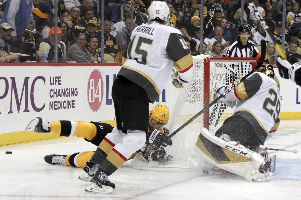 Pittsburgh Penguins' Zach Aston-Reese, bottom left, slides past Vegas Golden Knights goaltender ...