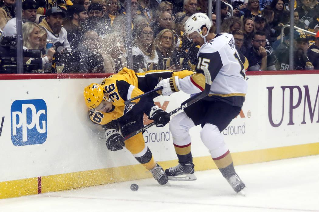 Vegas Golden Knights' Jon Merrill (15) checks Pittsburgh Penguins' Joseph Blandisi (36) into th ...