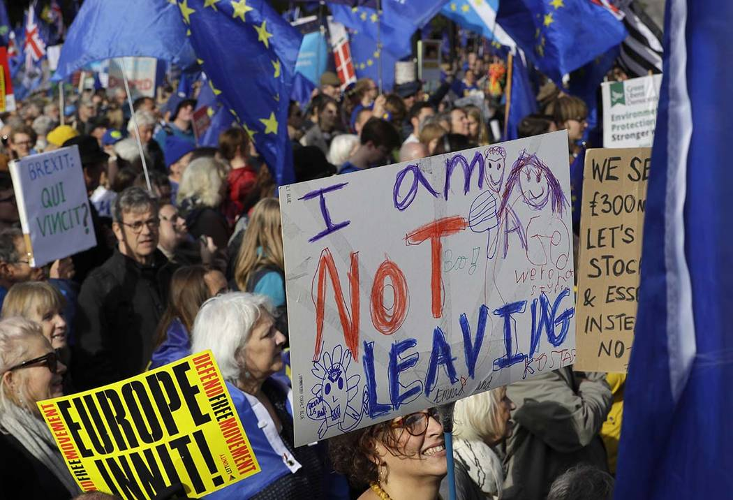 Anti-Brexit supporters carry signs and EU flags during a march in London, Saturday, Oct. 19, 20 ...