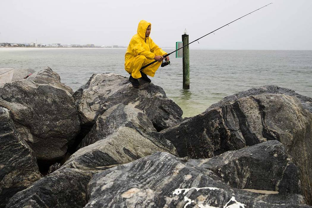 Michael Foster fishes as Tropical Storm Nestor approaches, Friday, Oct. 18, 2019 in Mexico Beac ...