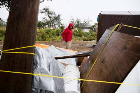 Chris Anderson ties down building materials and other objects from his lawn as Tropical Storm N ...