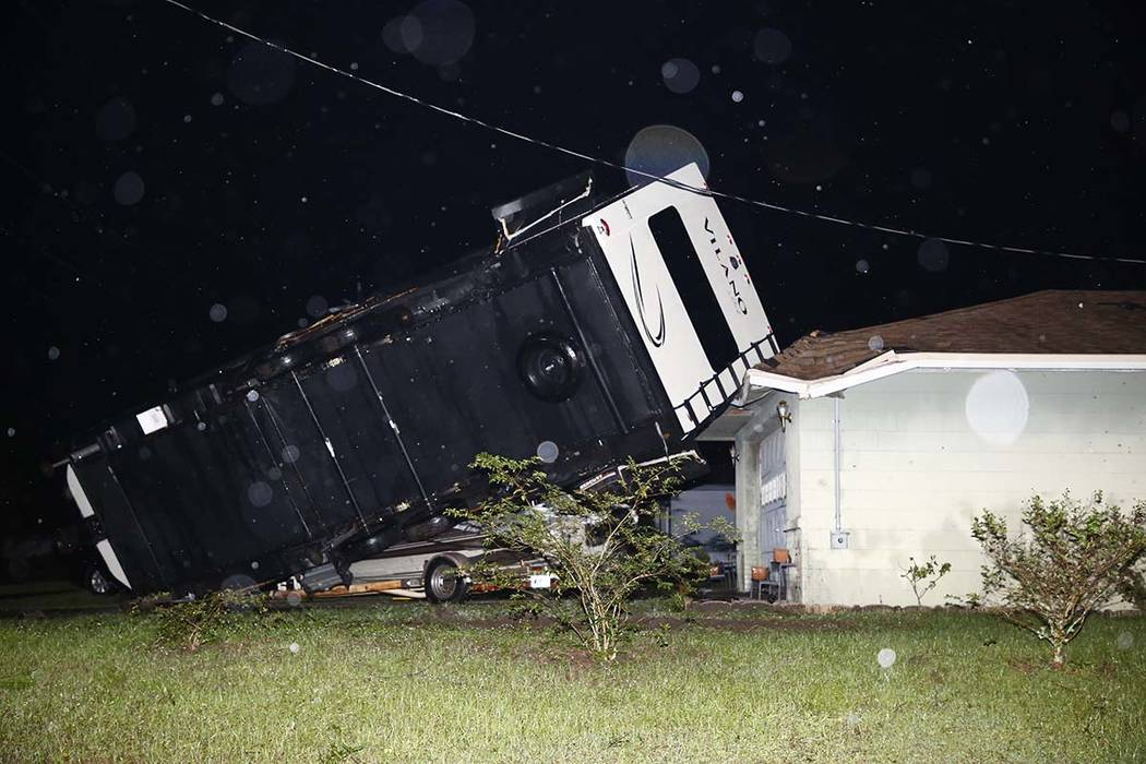 A camper rests on top of a boat trailer and the corner of a home as Tropical Storm Nestor passe ...