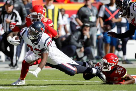 Houston Texans running back Carlos Hyde (23) is held back by Kansas City Chiefs cornerback Char ...