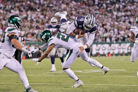 Dallas Cowboys quarterback Dak Prescott, top, runs the ball during the second half of an NFL fo ...