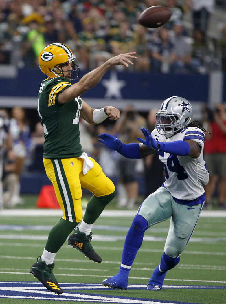 Green Bay Packers quarterback Aaron Rodgers (12) throws a pass as the Dallas Cowboys' Jaylon Sm ...