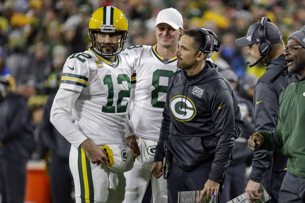 Green Bay Packers quarterback Aaron Rodgers (12) and head coach Matt LaFleur, third from left, ...