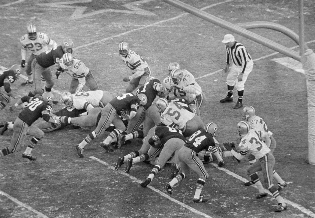 With seconds remaining, quarterback Bart Starr (15), Green Bay Packers, bulls way behind the Pa ...