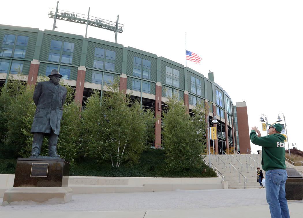 A fan takes a photo of the Vince Lombardi statue outside of Lambeau Field in Green Bay, Wis., F ...