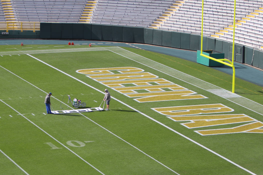 Workers paint hash marks on Lambeau Field in preparation for Sunday's game between the Green Ba ...