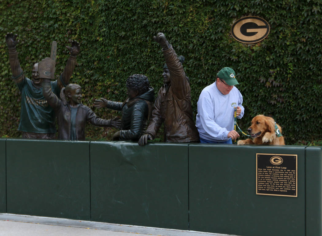 Packers season ticket holder John Nienaber, of Lakeside Park, Ky., tries to get his golden retr ...