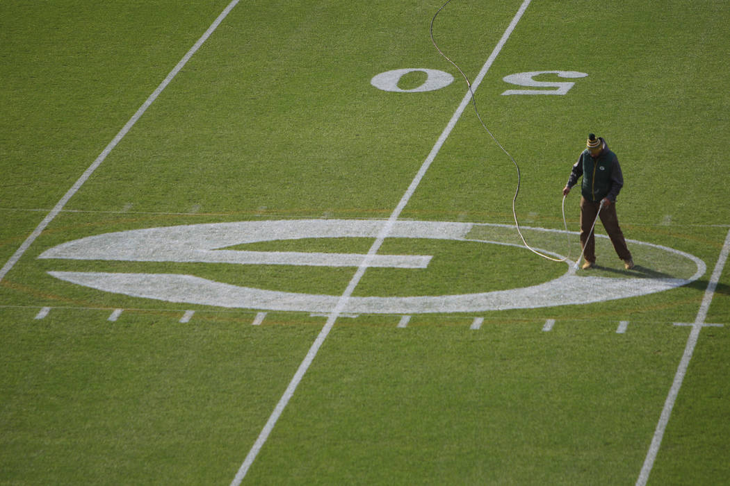 A worker paints the Packer logo at the 50 yard line of Lambeau Field in preparation for Sunday' ...