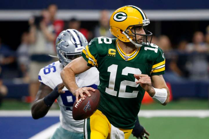 Green Bay Packers quarterback Aaron Rodgers (12) scrambles out of the pocket as Dallas Cowboys ...