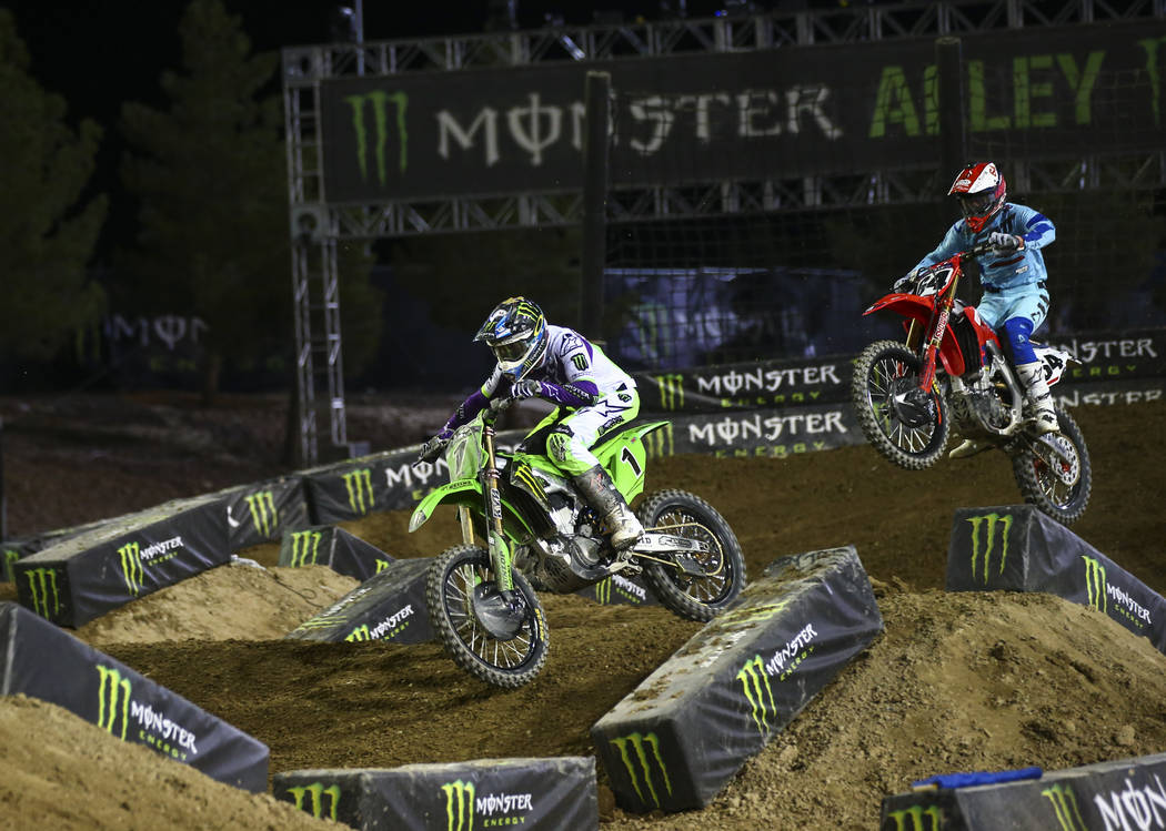 Eli Tomac (1) rides past Vince Friese (64) during the first round of the Monster Energy Cup Sup ...