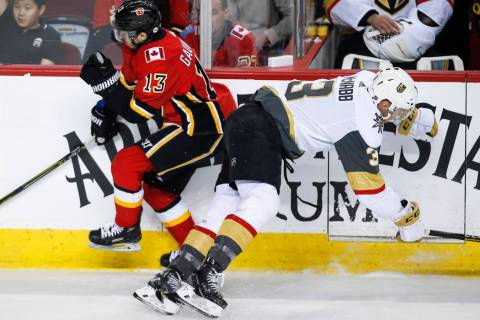 Vegas Golden Knights' Brayden McNabb, right, checks Callgary Flames' Johnny Gaudreau during fir ...