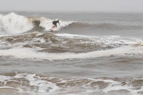 A surfer finds a wave in Mexico Beach, Fla. after Tropical Storm Nestor hit the town on Saturda ...