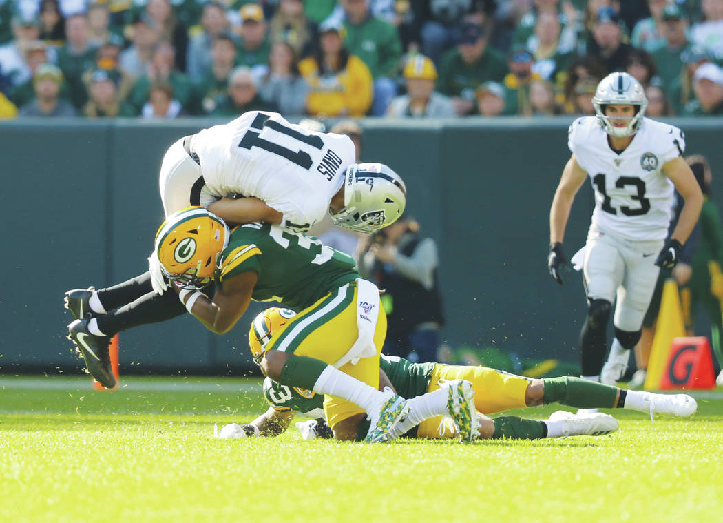 Oakland Raiders wide receiver Trevor Davis (11) tries to leap over Green Bay Packers strong saf ...