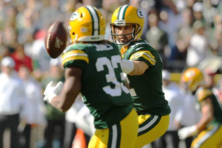 Green Bay Packers quarterback Aaron Rodgers (12) flicks the football to running back Aaron Jone ...