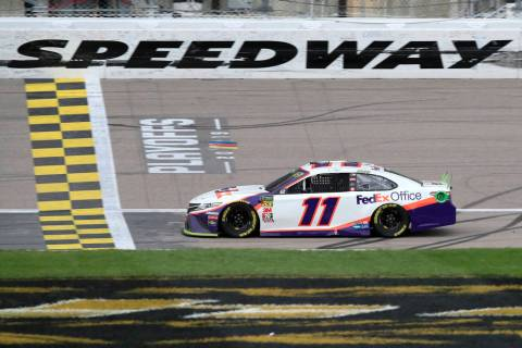 Denny Hamlin (11) crosses the finish line to win a NASCAR Cup Series auto race at Kansas Speedw ...