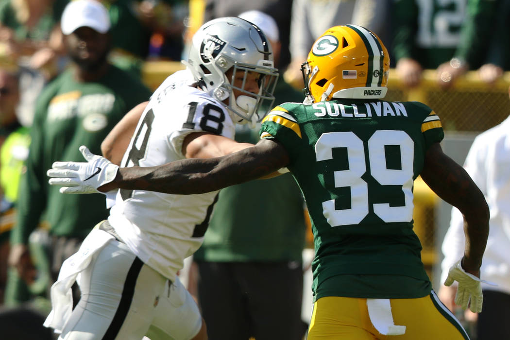 Oakland Raiders wide receiver Keelan Doss (18) stiff arms Green Bay Packers defensive back Chan ...