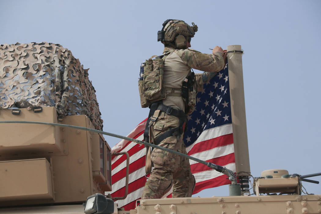 American soldier mount the U.S. flag on a vehicle near the town of Tel Tamr, north Syria, Sunda ...