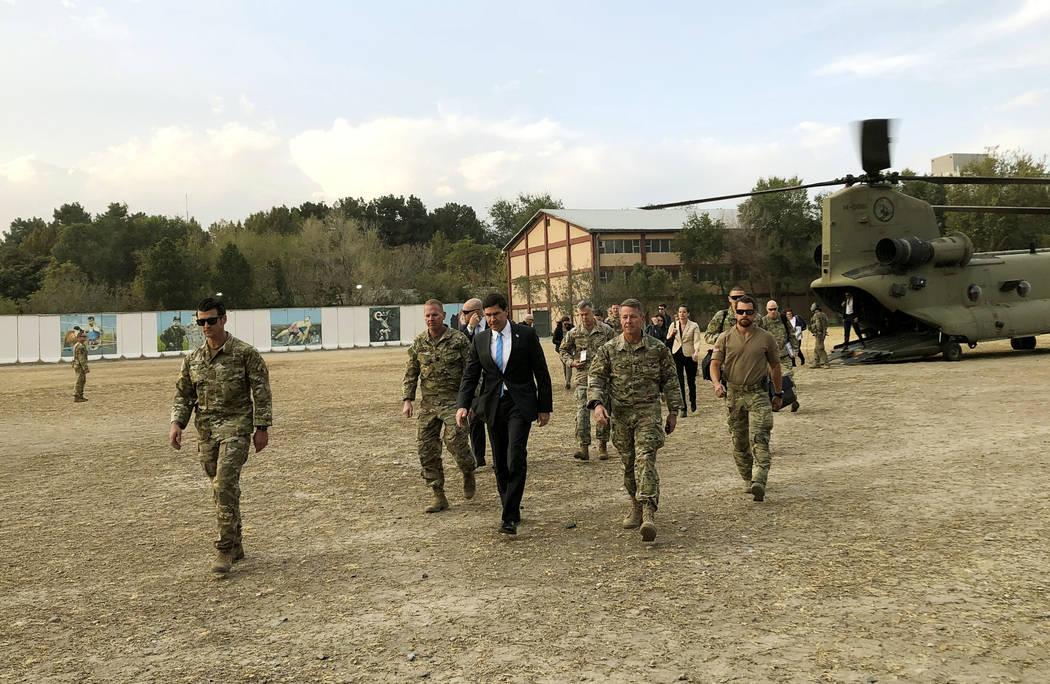 U.S. Defense Secretary Mark Esper, center, walks Gen. Scott Miller, right, chief of the U.S.-le ...