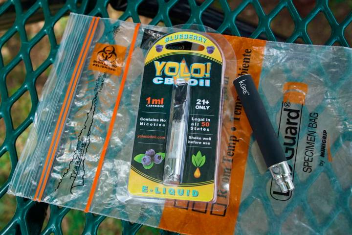 In a May 8, 2019, file photo, a Yolo! brand CBD oil vape cartridge sits alongside a vape pen on ...