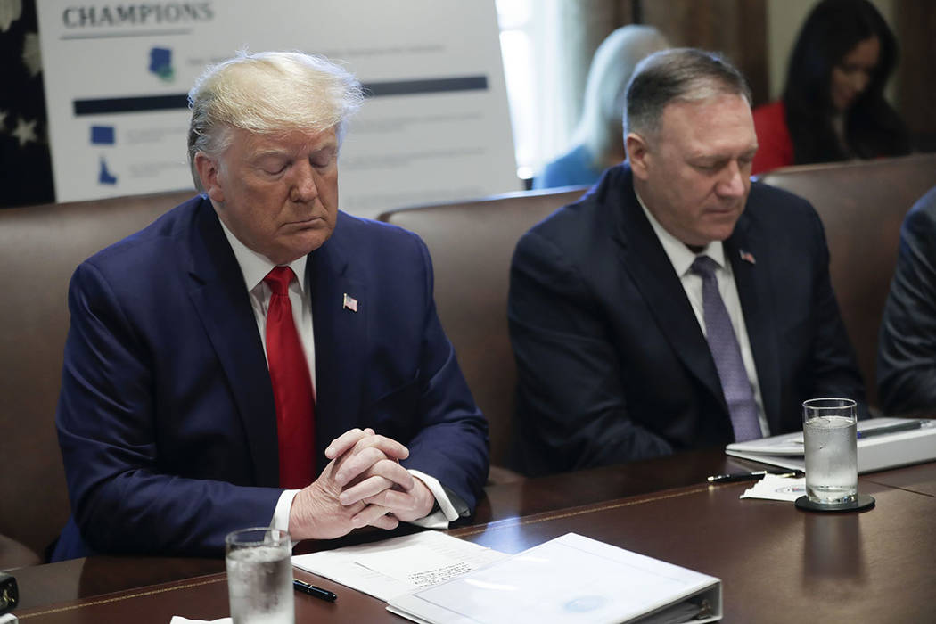 President Donald Trump, left, and Secretary of State Mike Pompeo, right, pause during an openin ...