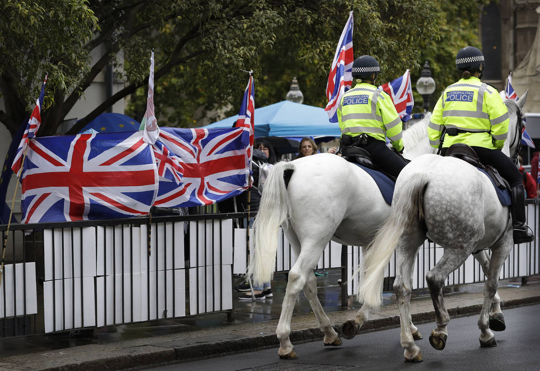 Police horses pass a confusion of flags and banners both pro and against Brexit, outside Parlia ...