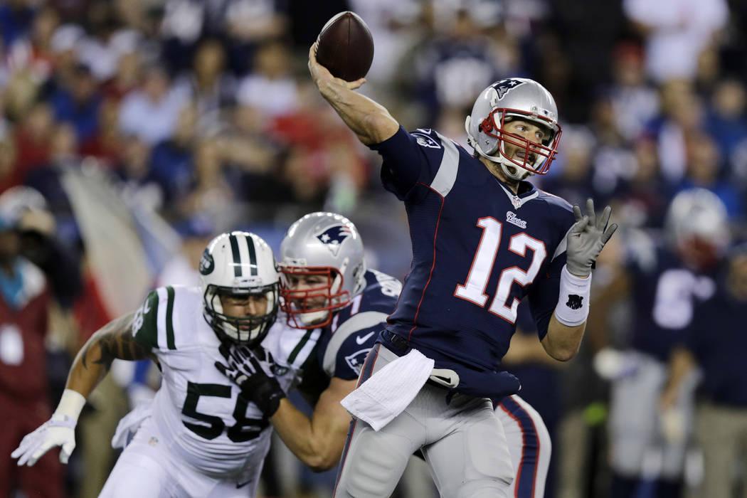 New England Patriots quarterback Tom Brady throws as New York Jets defensive end Jason Babin (5 ...