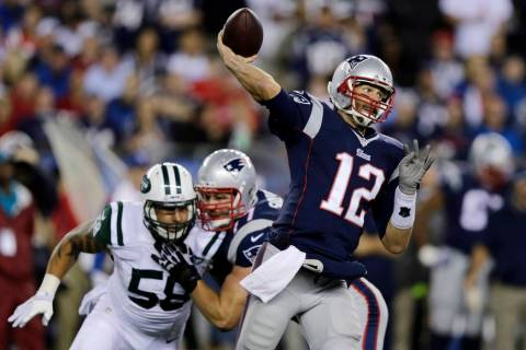 New England Patriots quarterback Tom Brady throws as New York Jets defensive end Jason Babin (5 ...
