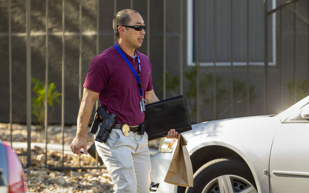 An officer departs the scene carrying a brown bag during a possible officer involved shooting a ...