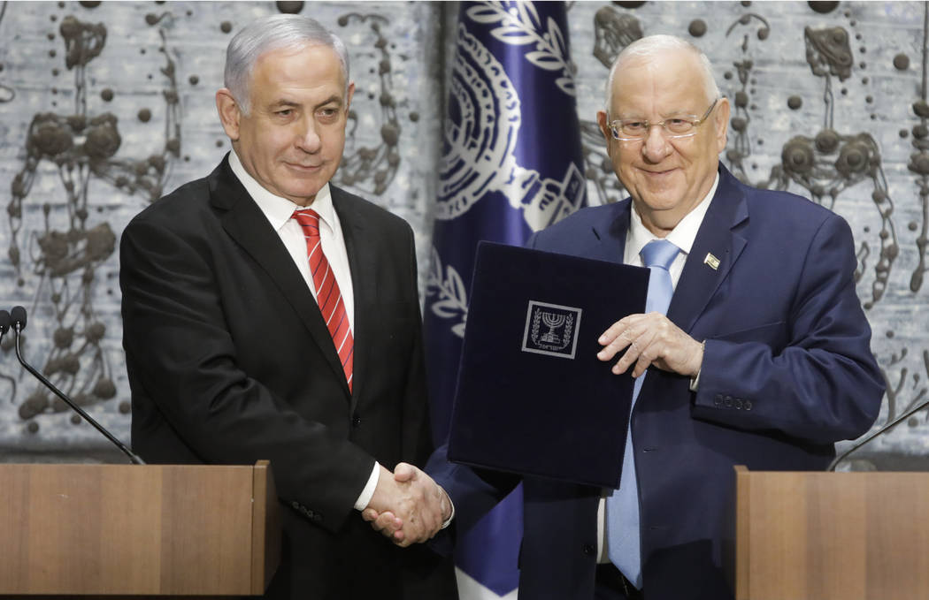 FILE - In this Sept. 25, 2109 file photo, Israeli President Reuven Rivlin, right, shakes hands ...