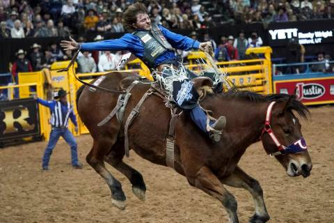 Rusty Wright of Milford, Utah (20) competes in the saddle bronc riding event during the eighth ...