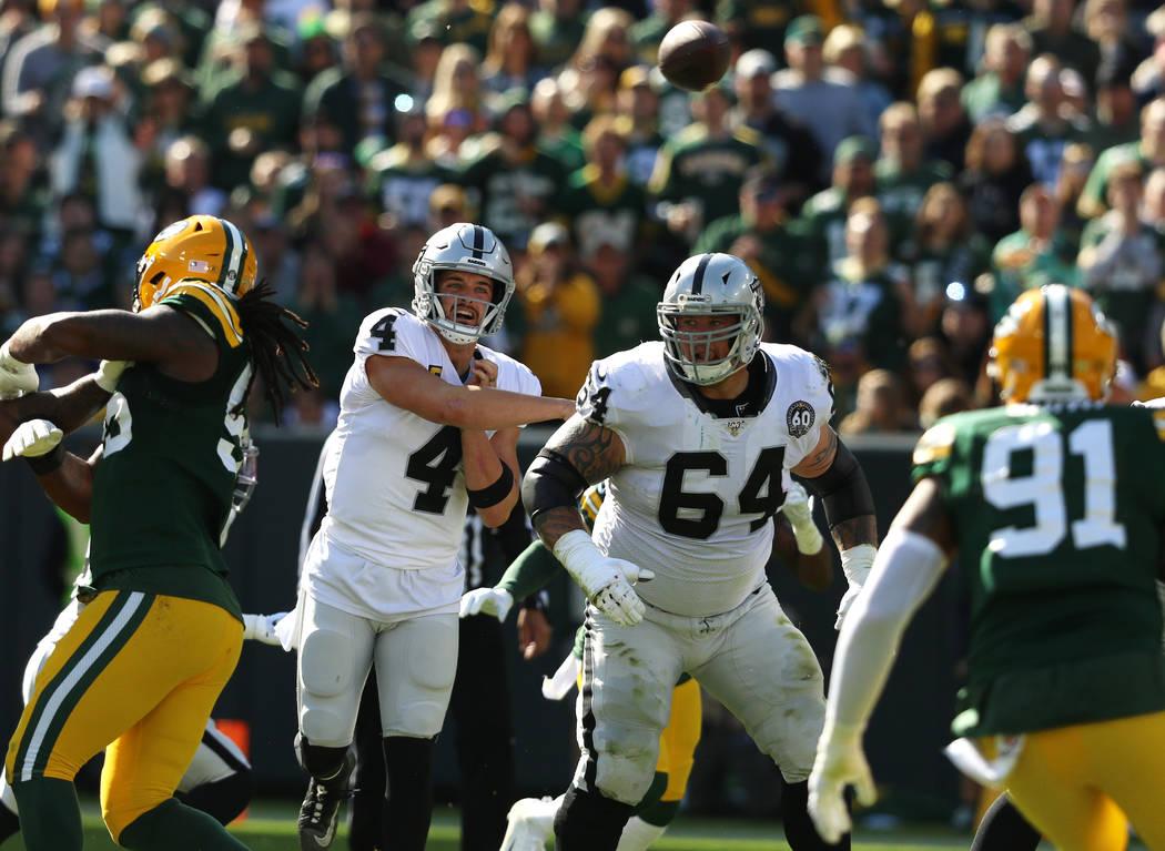 Oakland Raiders quarterback Derek Carr (4) throws the football as offensive guard Richie Incogn ...