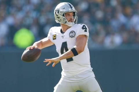 Oakland Raiders quarterback Derek Carr looks to pass during an NFL football game between the Gr ...