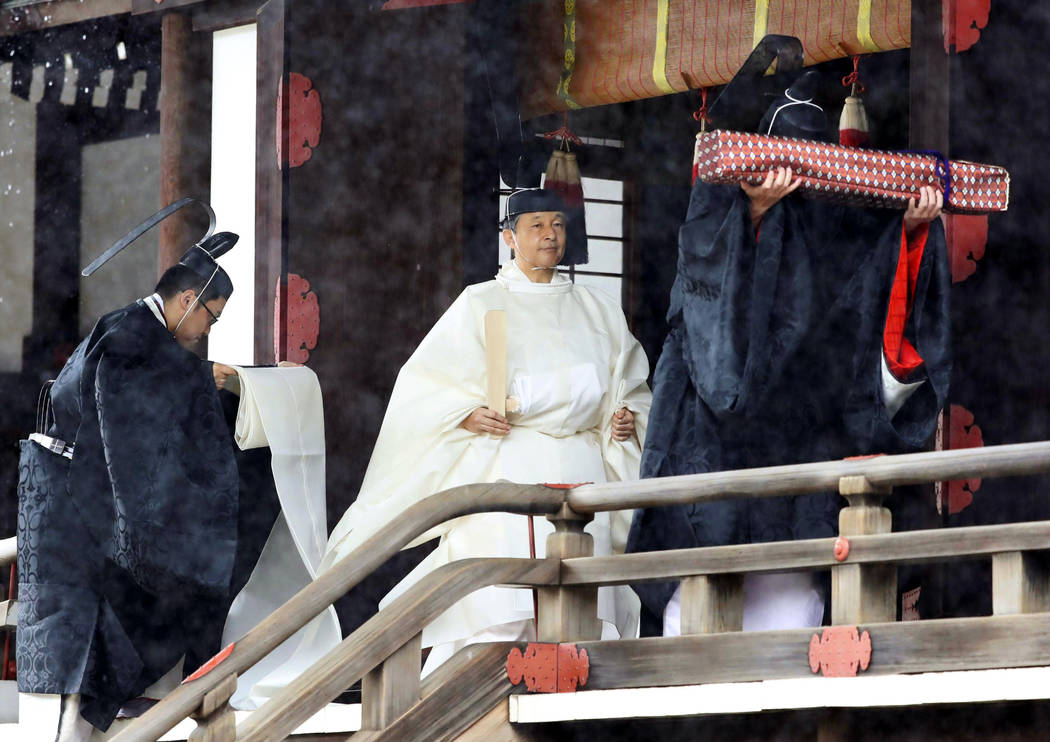 """Japan's Emperor Naruhito, in a white robe, leaves after praying at """"Kashikodokoro&#x201d ..."""